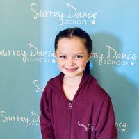 Surrey Dance School pupil in front of logo banner
